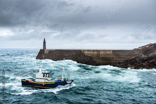 Fishing Vessel under Storm.arriving at pier.  It's a boat or ship used to catch fish in the sea. Fishing can be affected by storms because of conditions like strong wind, precipitations or rain.