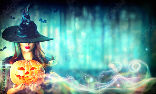 Fotografie, Obraz  Sexy witch with a Halloween pumpkin Jack-o-lantern in a dark forest