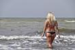 Beautiful blonde walks into the sea water