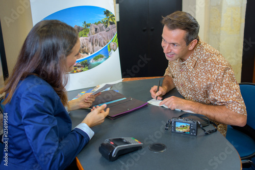 Man writing out cheque in travels agents