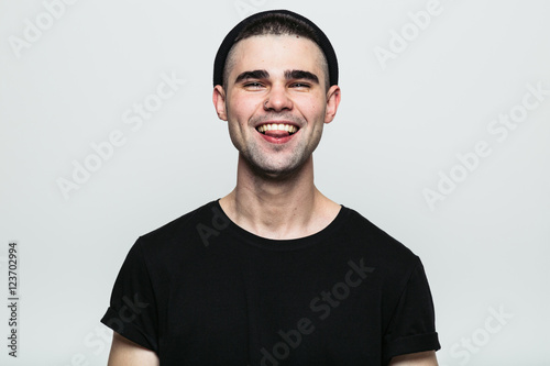 Valokuva  Portrait of young man showing his pierced tongue on white background