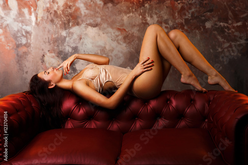 Photo  sexy girl on the red sofa. playful mood