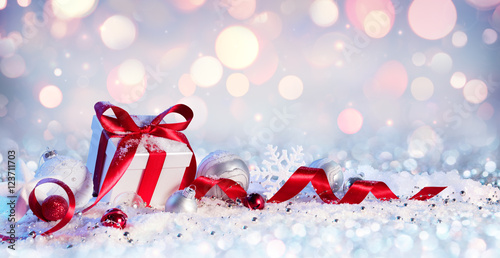 Poster Gift Box And Baubles On Snow With Shiny Background