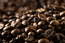 Sea Of Dark Roasted Coffee Beans Flowing Into Background