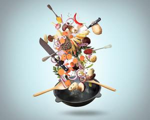 Fototapeta samoprzylepna Large iron skillet with falling vegetables and mushrooms