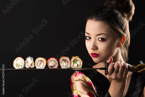 Tuinposter Sushi bar beautiful girl samurai with sword and rolls