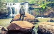 The man standing with camera at Tad Huang Waterfall,become the murder line between Thai-Laos at at Phu Suan Sai National Park,Loei Province.Processed in vintage style,soft focus.