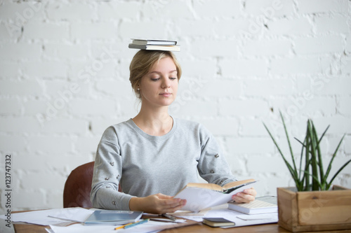 Foto Portrait of a young attractive woman at the desk with books on her head, sitting straight, reading a book