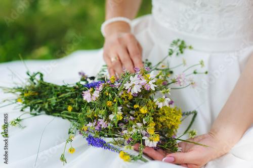 Fototapeta Bride with a bouquet of wildflowers obraz na płótnie