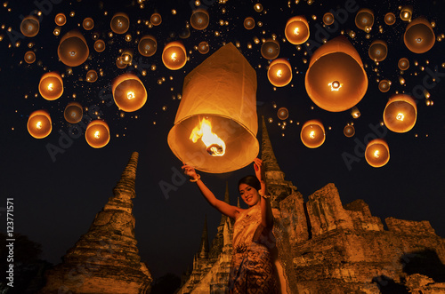 Thai woman with floating lamp in Ayuthaya historical park, with Wat Phra Sri Sanphet temple background, Thailand