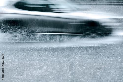 Plakat droga miejska podczas deszczu. jazda samochodem z prędkością przez kałuże deszczu. niewyraźny ruch.