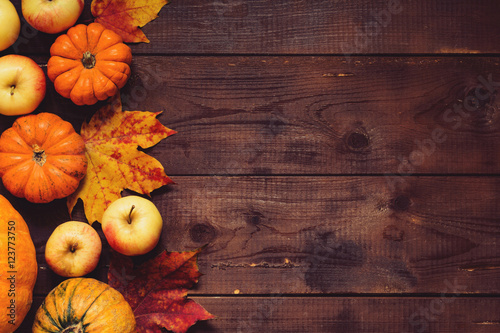 Fototapeta Thanksgiving background: Apples, pumpkins and fallen leaves on wooden background. Copy space for text. Halloween, Thanksgiving day or seasonal background. Design mock up. obraz