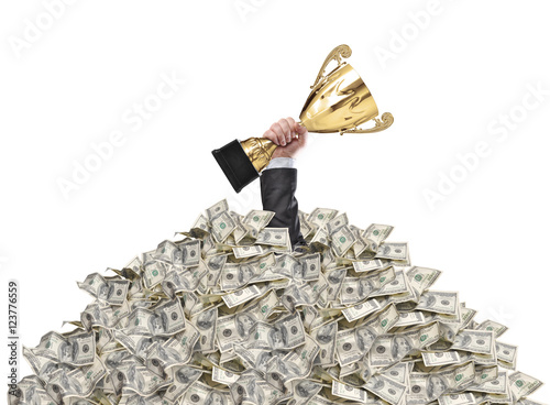 Fényképezés  hand of a man stuck in a pile of money holding a cup trophy abov