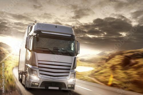 Fototapeta Ciężarówka na wiejskiej drodze przy zmierzchem