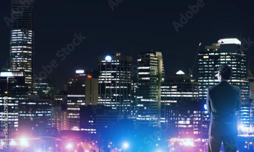 Fototapeta Businessman viewing night glowing city obraz na płótnie