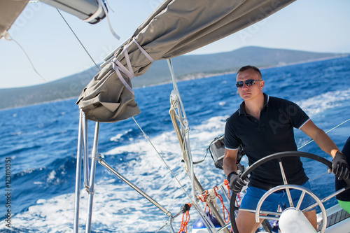 Voile Young sailor skipper manages sailing vessel during regatta race in the open sea.