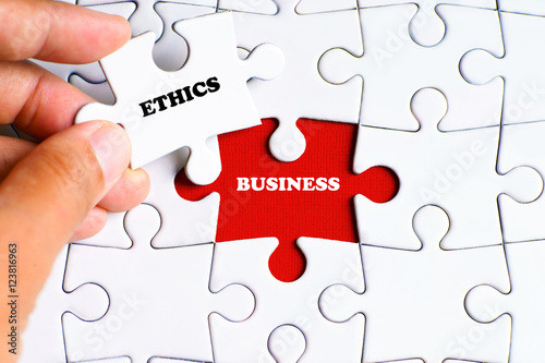 "Fotografie, Obraz  ""BUSINESS"" word on missing puzzle with a hand hold a piece of ""ETHICS"" word puzz"