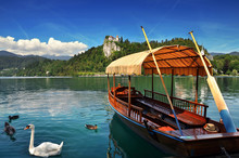 Bled Lake Slovenia,Europe.Traditional Pletna Boat On The Lake With Swans. In The Background Is The Famous Old Castle On The Cliff