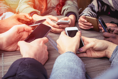 Fotomural  hands on smart phones - a group of friends using mobile phones sitting at the ta