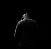 Black And White Silhouette Of A Hooded Man, Who Turned Away, Isolated On Black Background