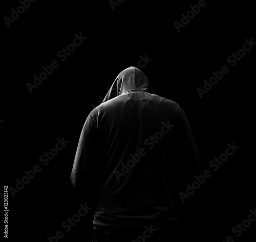 Fotomural  Black and white Silhouette of a hooded man, who turned away, isolated on black b