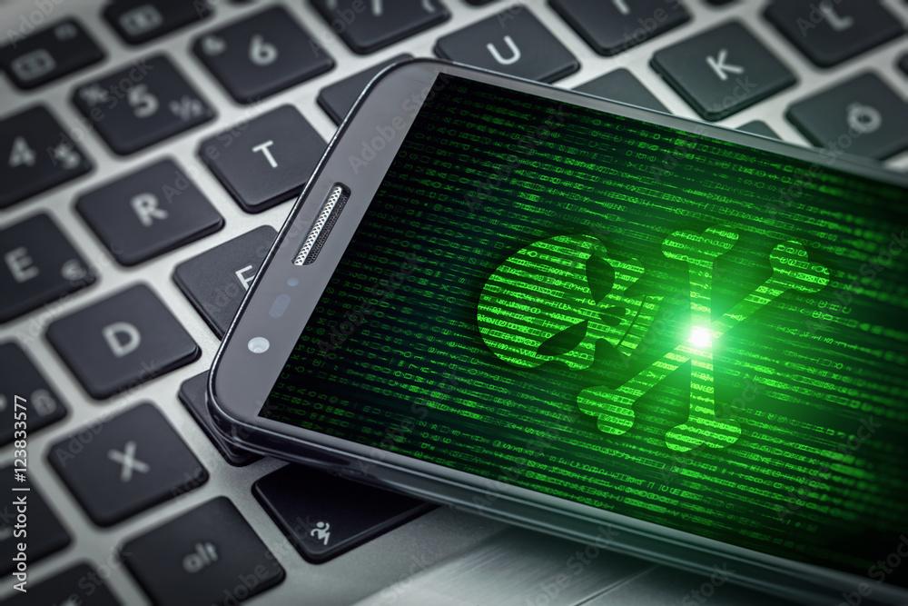 Fototapeta skull of death on smartphone screen. Hacked mobile phone on laptop computer
