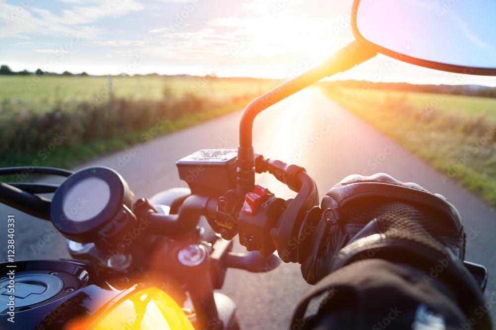Fototapeta Motorrad fahren auf Landstrasse im Sonnenuntergang bei blauem Himmel