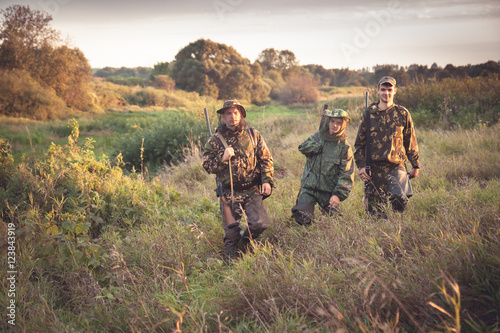 Poster Chasse hunters going through tall garass in rural field at dawn during hunting season