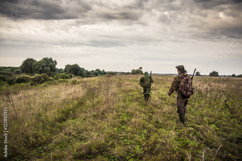 Foto op Canvas Jacht Hunters going through rural field with dramatic sky during hunting season