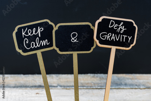 Valokuva  Keep Calm and Defy Gravity message written with chalk on mini blackboard labels