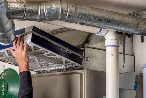 Fotomural  Man replaces a filter in a furnace