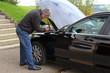 Ein Mann füllt an einem Auto Scheibenwisch-Wasser nach