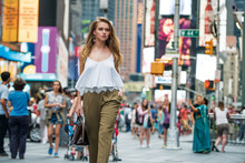 Attractive Young Adult Woman Walking Around Crownd On New York City Street And Carrying A Bag Wearing White Top And Pants