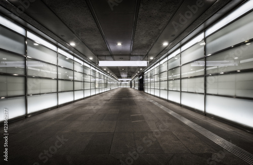 Fotografie, Tablou  Empty corridor at night with glass illuminated walls