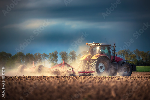 Farmer in tractor preparing land with seedbed cultivator плакат