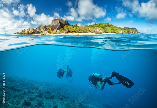 Fotobehang Duiken Divers below the surface in Seychelles