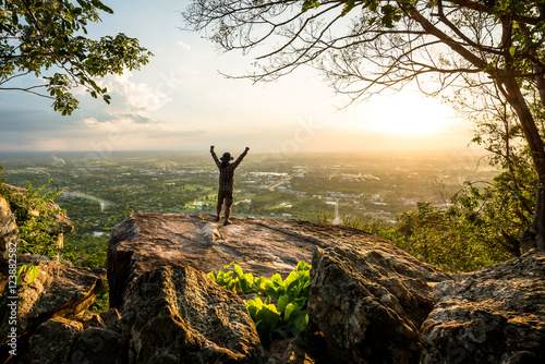 Obrazy na płótnie Canvas Resting adult man at the top of rock with aerial view