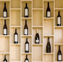 Variety Bottles Of Wine And Champagne In A Wooden Display Case In The Store