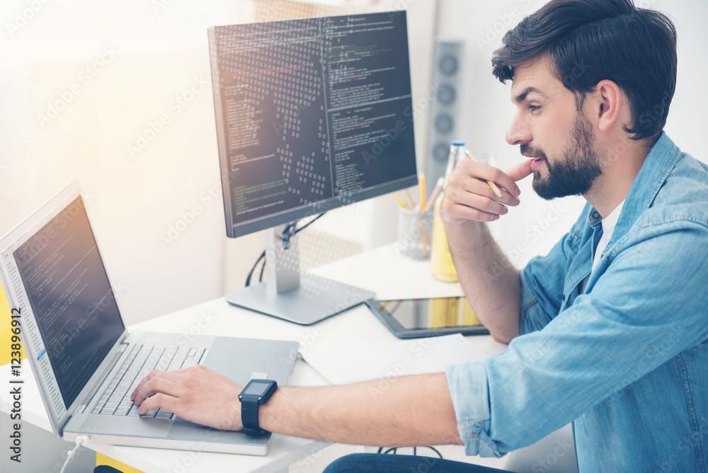 Fototapeta Young man working as a programmer