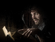 Necromancer Casts Spells From Thick Ancient Book, Behind Transparent Glass Covered By Water Drops On A Dark Background