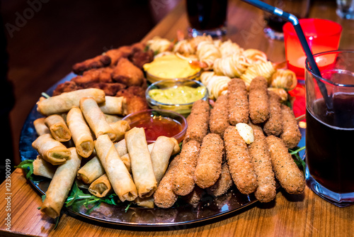 Tela Silver plate full of appetizers finger food starters at party.