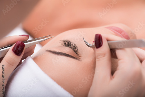 Obraz Beautiful young woman during eyelash extension - fototapety do salonu