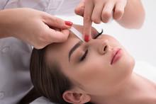 Young Woman Tweezing Her Eyebr...