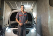 Portrait of mechanic in front of car in a garage
