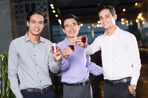 Stampe  Three Smiling Men Raising Glasses in Bar
