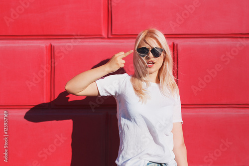Fotografija  teenage girl in white t-shirt and shades showing middle finger