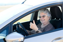 Happy Cheerful Elderly Senior Woman Driving Her Car Showing Thumbs Up