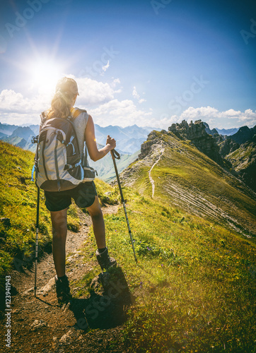 Strong female hiker with backpack pauses on path Wall mural