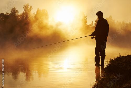 Fotografía fisher fishing on foggy sunrise