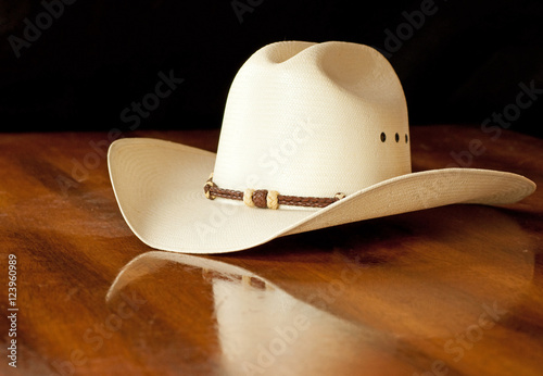 White straw cowboy hat with a hatband on a wooden table against dark  background fb0157b0d5d6